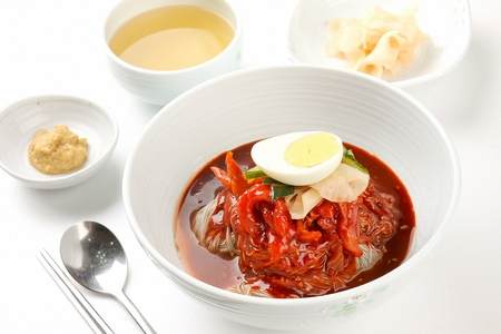 Kodari bibim naengmyeon, korean noodle cuisine, noodles and half-dried pollacks mixed in spicy sauce, on white bowl