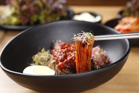 Chopsticks grabbing bibim makguksu, noodles mixed with spicy sauce, boiled eggs, on black bowl Imagens