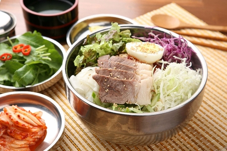 Korean cuisine, bibim guksu, noodles with vegetables, boiled eggs, boiled meat, on silver plate