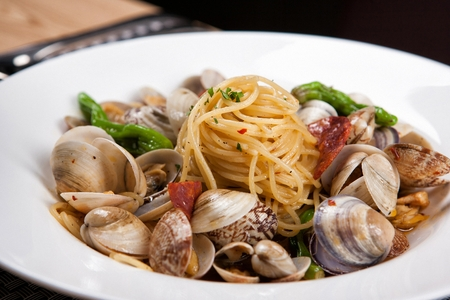 Oil pasta with oysters and vongole pasta on white bowl