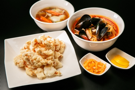 Jjampong, spicy chinese noodle dish with various seafood such as mussels, abalone, and scallop, on white bowl and radish