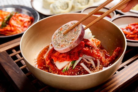 Chopsticks grabbing Korean cuisine Bibim Naengmyeon, chilled buckwheat noodles garnished with cold slices of beef, fresh skate, and radish or cucumber. Served with a spicy gochujang mixing sauce