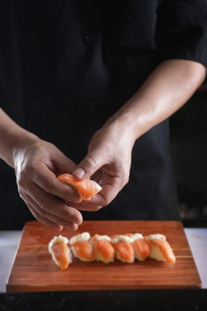 Hand of chef clothed in black garment placing salmon sushi on a wooden cutting board Reklamní fotografie