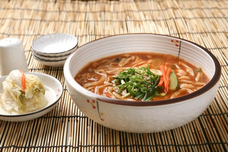 Jang kalguksu, korean noodle cuisine, thick noodles boiled in spicy broth, on white bowl Stock Photo