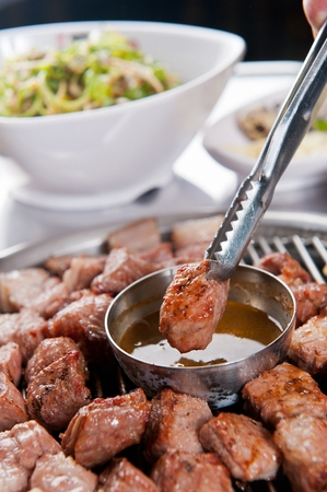 Tongs grabbing grilled pork neck slice and dipping in sesame oil seed with salt