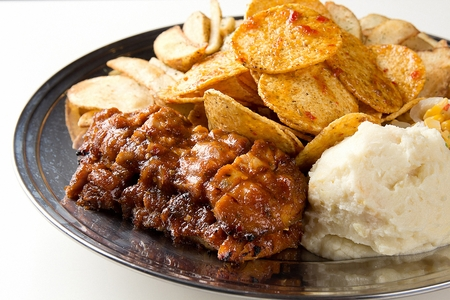 Closeup of BBQ plate with nachos, corn salad, marinated pork, mashed potato salad, fries Imagens - 111935779