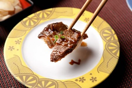 Chopsticks grabbing beef sushi, on a round plate
