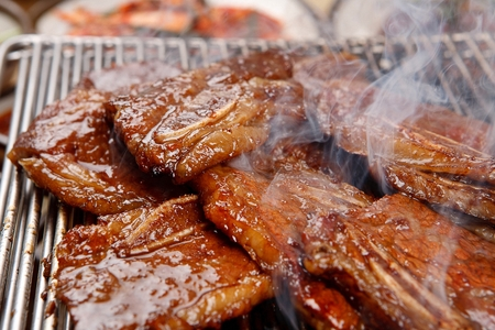 Marinated LA rib being grilled Imagens