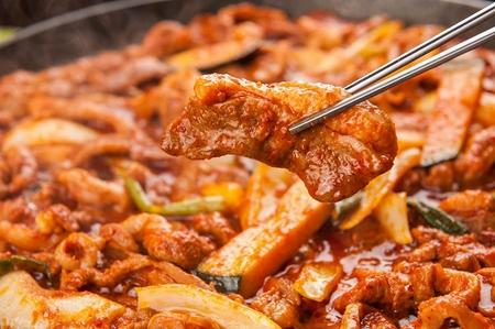 Chopsticks grabbing ori bulgogi, a Korean cuisine, duck and vegetables stir-fried with spicy sauce on black iron plate