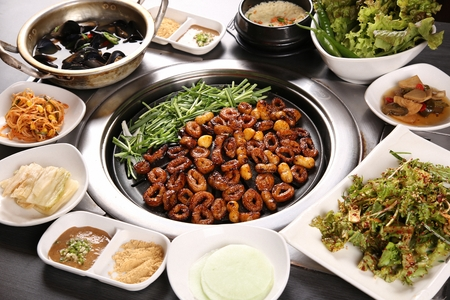 Marinated pork makchang, chives, side dishes being grilled on a black grill