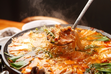 Ladle with gopchang jeongol, a spicy Korean cuisine, vegetables and tripes boiled in a black pot
