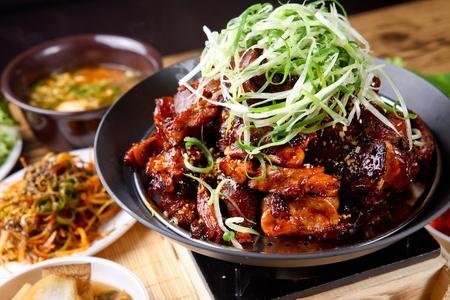 Spicy jokbal, a spicy Korean cuisine, with scallions, on an iron plate