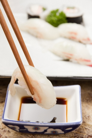 Chopsticks grabbing flatfish sushi and dipping in soy sauce