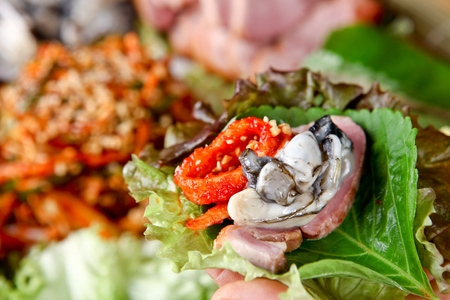 Smoked duck wrapped with lettuce and sesame leaf, with oyster, radish kimchi Stockfoto