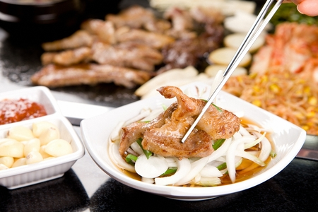 Chopsticks grabbing grilled pork cheek meat, dipping in soy sauce with onions and chives