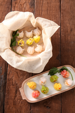 Dim sum, yellow, pink, white, green Chinese dumplings, on a plate and in a steamer