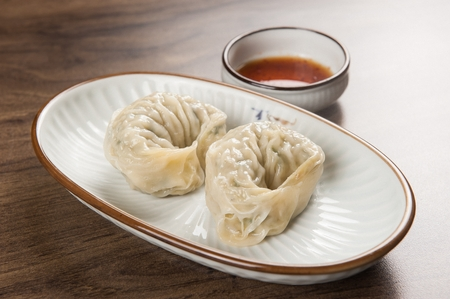 Steamed king-sized dumpling and soy sauce, on a white plate
