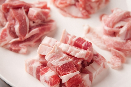 Pork belly, pork cheek meat, thinly sliced pork belly, on a white round plate Stock Photo