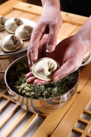 Chef's hands making dumpling by filling vegetables and meat in thin wrapping