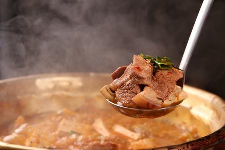 Ladle picking up Spicy Korean-style Kimchi stew(Kimchi-jjige), cooked with kimchi, pork and tofu