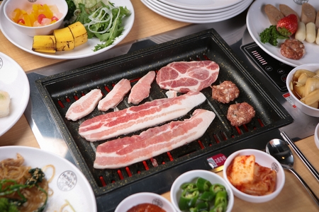 Meat and side dishes on grill