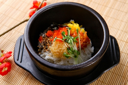 Al-bap, rice with thinly sliced vegetables and flying fish roe, in black pot