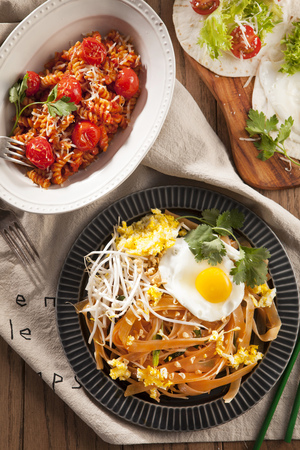 Rotini pasta with tomates, served with stir-fried rice noodles