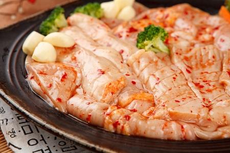 Spicy marinated pork entrails, garlic, on black plate Standard-Bild