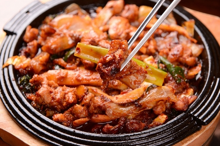 Spicy stir-fried chicken with welsh onions, on grill