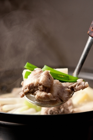 Ladle scooping up broth from dak-gomtang, korean soup dish with cut chicken meat boiled as its broth