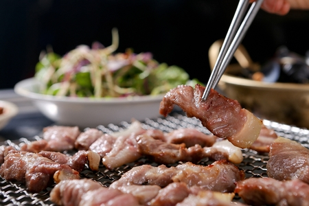 Chopsticks picking up pork belly being grilled on charcoal grill