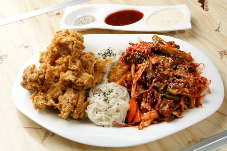 Spicy sea snails salad, noodles and fried chicken on white plate Stock Photo