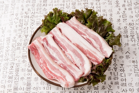 Pork belly on lettuce on round plate