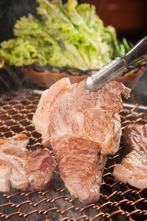 Pincers turning pork neck being grilled on charcoal grill Stok Fotoğraf