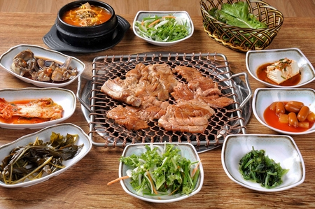 Marinated pork spareribs being grilled on charcoal grill, with side dishes Stockfoto