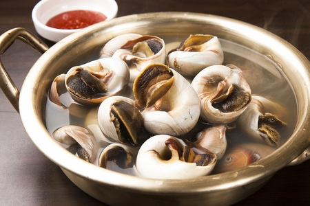 Steamed whelk in nickel silver pot Stock Photo