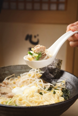 Spoon scooping up Tonkotsu ramen, japanese noodle dish with broth made of boiled pork bones Banque d'images