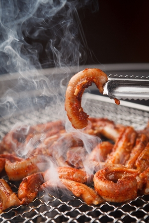 Pincers picking up marinated eels being grilled on charcoal grill Stock Photo
