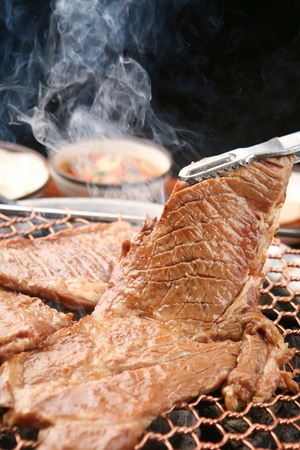 Pincers turning marinated pork spareribs being grilled on charcoal grill