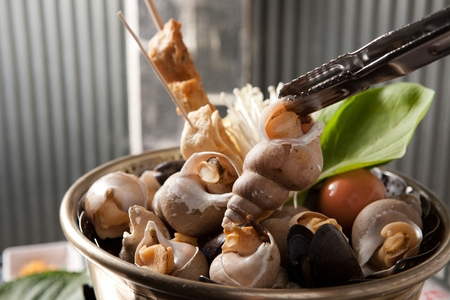 Steamed whelk, fish cake skewers, greens, winter mushrooms in nickel silver pot Stock Photo