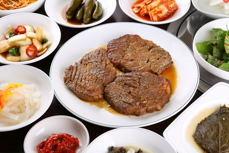 Marinated pork spareribs on white plate, side dishes