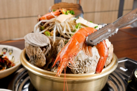 Pincers picking up shrimp from steamed seafood, with shrimp, oysters, scallops and bean sprouts in nickel silver pot Фото со стока