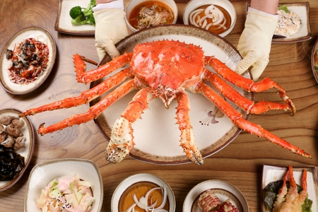 Chef holding round white plate with steamed king crab