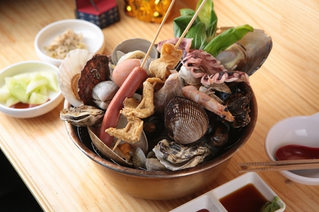Scallops, oysters, sausages, fish cakes skewers, shells, squid, greens in nickel silver pot Фото со стока