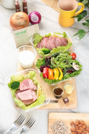 Chicken breast salad in disposable plastic container, on wooden cutting board Banque d'images