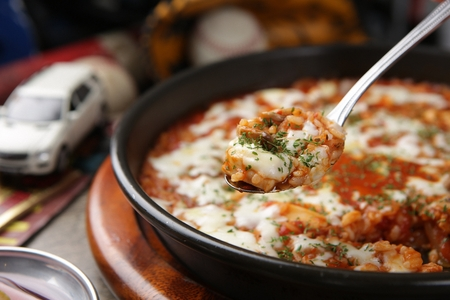 Spoon scooping tomato seafood risotto with cheese, from black oven plate Stock Photo