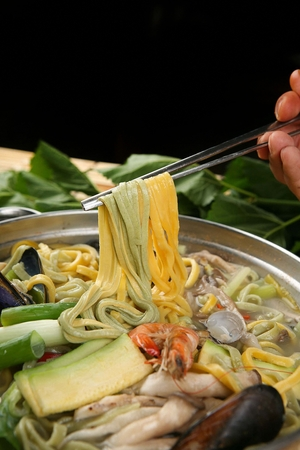 Chopsticks picking up mulberry leaves seafood noodles, noodles with seafood broth with mulberry leaves Stok Fotoğraf