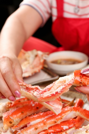 Chef defleshing legs of steamed king crab, on white plate Stockfoto