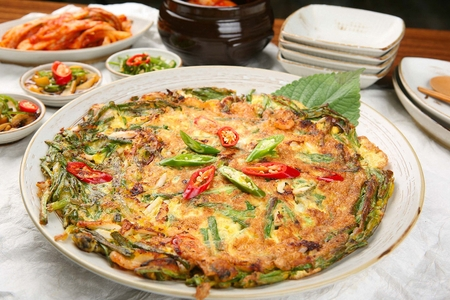 Seafood pancake, korean-style pancake with seafood, welsh onions, chili, on white plate