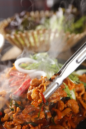 Pincers picking up spicy barbecued pork with vegetables, being grilled on black grill